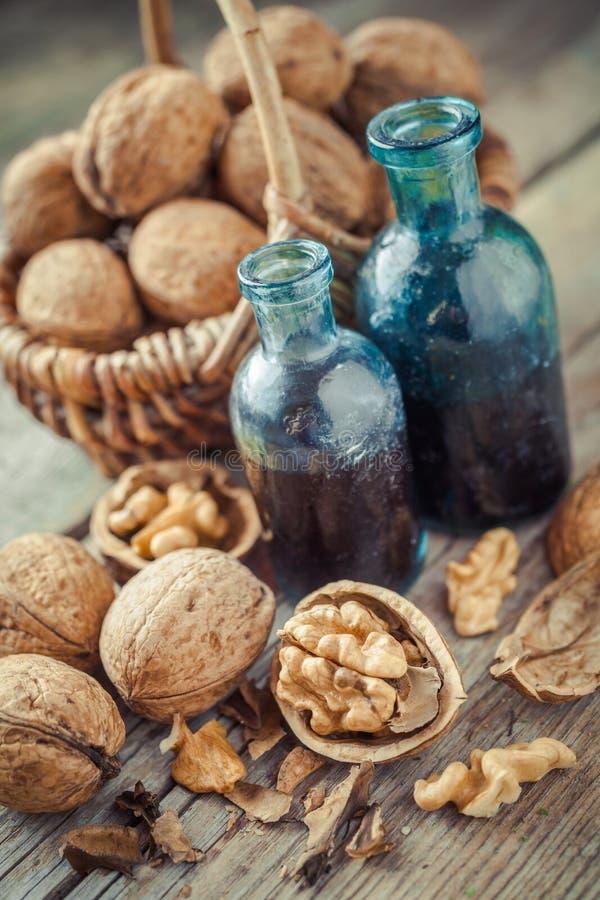 Valnötter i korg- och muttertinktur eller olja på den gamla tabellen royaltyfri bild