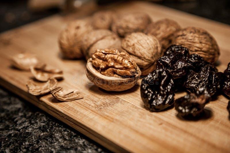 Valnötter nad torkade katrinplommonet på träbrädet för hälsa för man` s royaltyfria foton