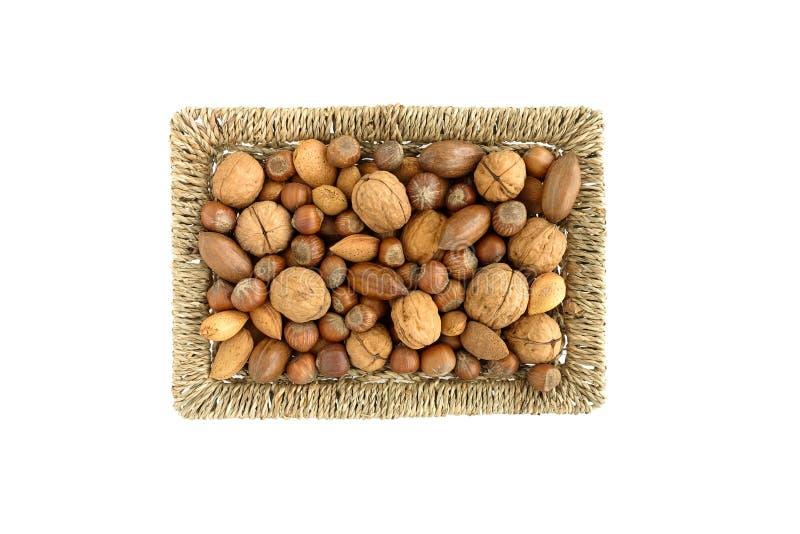Valnötter, pecannötmuttrar, hasselnötter och mandlar i en korg arkivbild