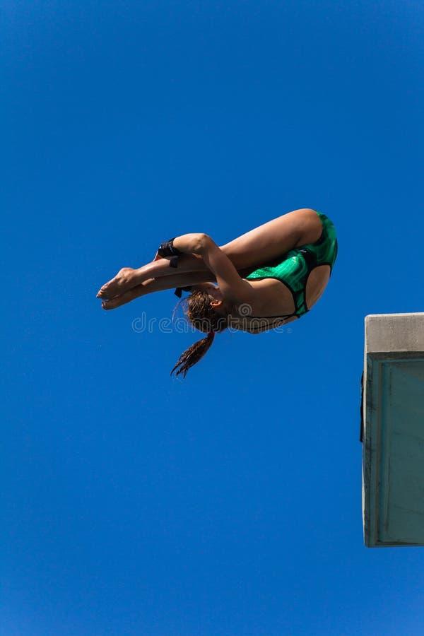 Valor de la muchacha del salto de la piscina de la plataforma acuático imagen de archivo