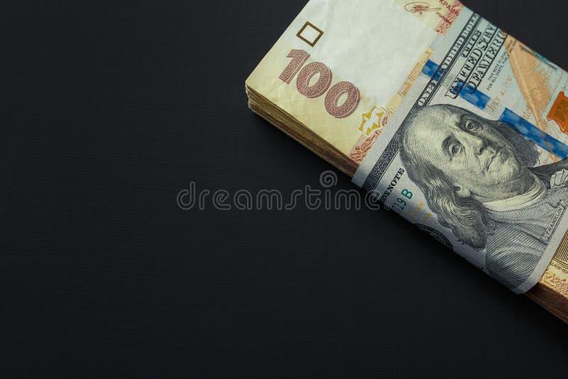 Valor do hryvnia ucraniano e de d?lares americanos Um bloco do hryvnia ucraniano envolveu cem notas de dólar foto de stock royalty free