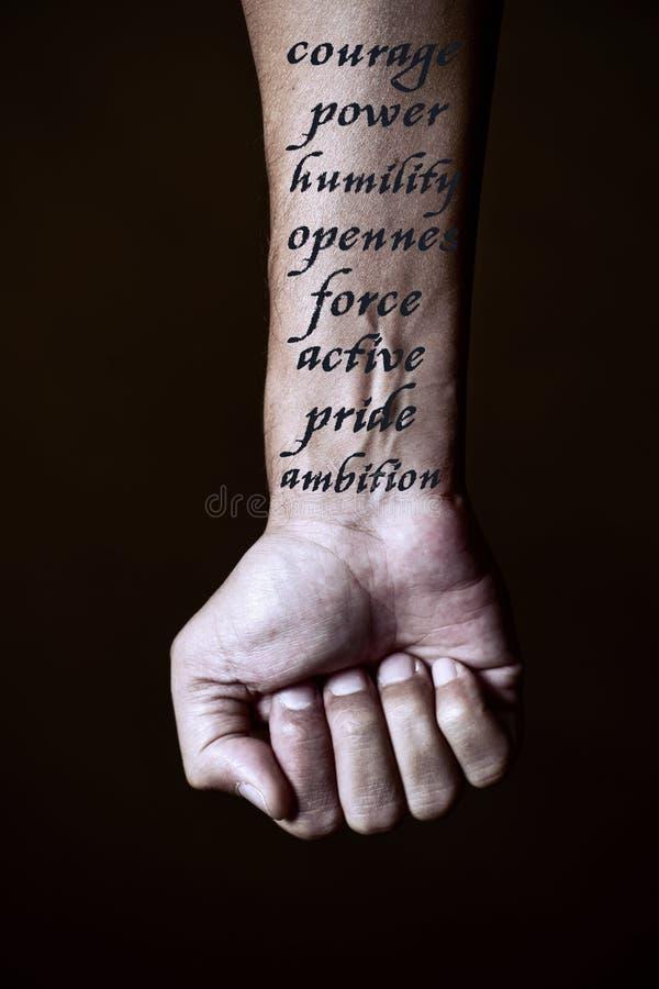 Valor, poder y algunas otras palabras en un antebrazo imagenes de archivo