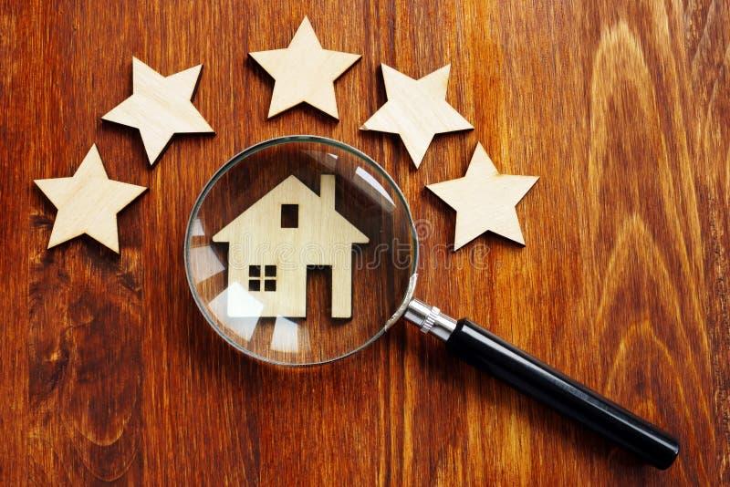 Valoración casera Casa con la lupa y la estrella cinco foto de archivo