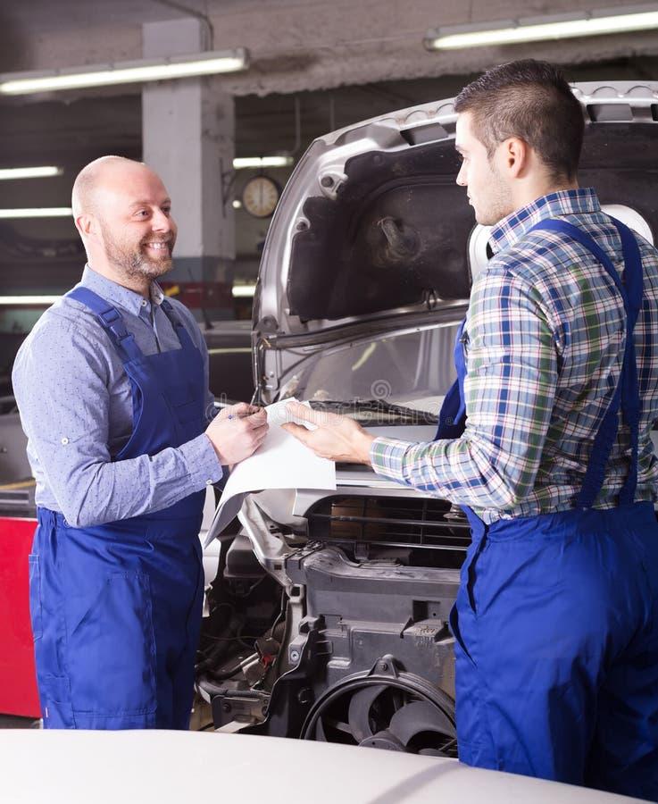 Valoración del daño para reparar el coche en el taller fotografía de archivo