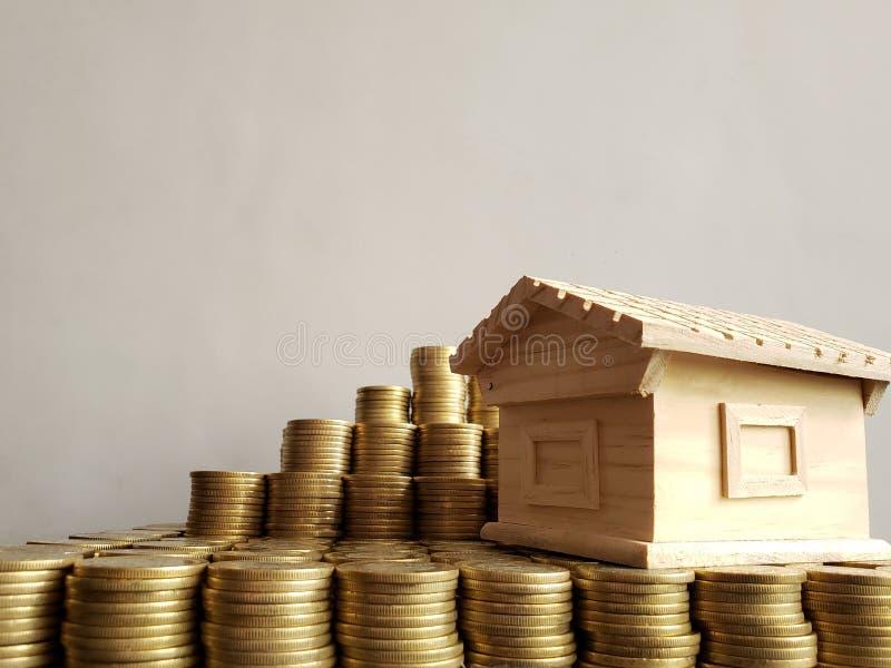 valore di una proprietà, monete impilate e una figura di legno di una casa immagini stock