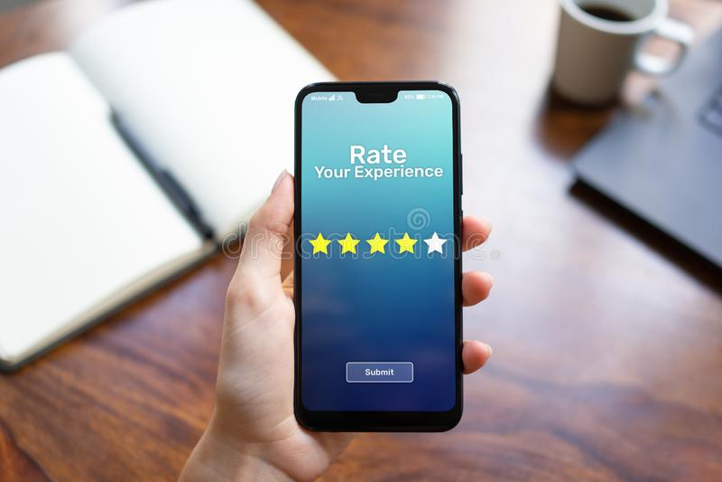 Valore sus estrellas del estudio cinco de la satisfacción del cliente de la experiencia en la pantalla del teléfono móvil Concept fotografía de archivo libre de regalías