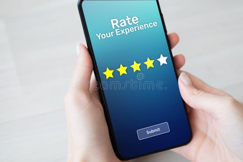 Valore sus estrellas del estudio cinco de la satisfacción del cliente de la experiencia en la pantalla del teléfono móvil Concept imagen de archivo