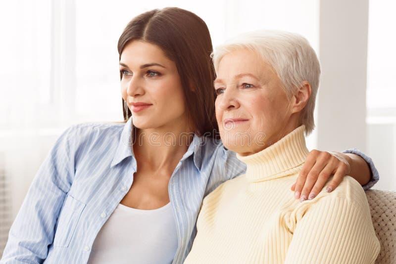 Valores familiares Filha que abraça a mãe e que olha de lado foto de stock royalty free