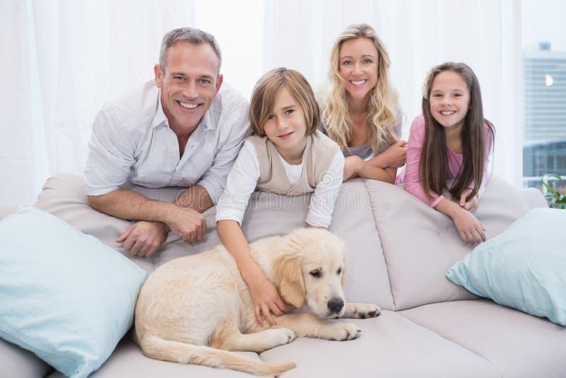 Valp som ligger på soffan med familjanseendet bakom royaltyfri foto