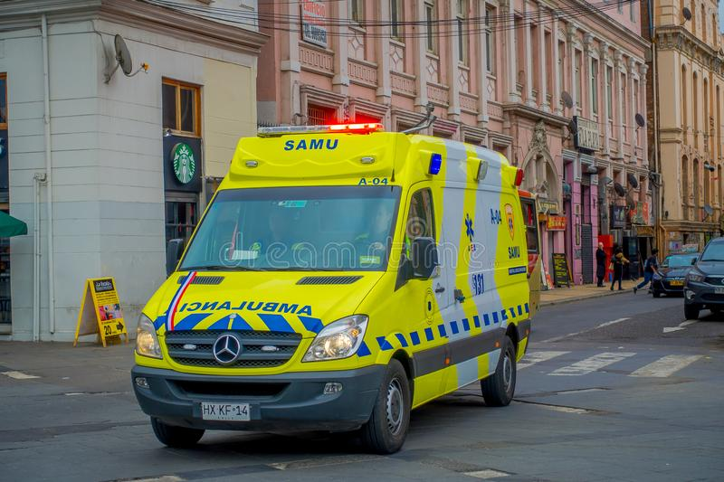 VALPARAISO, CHILE - SEPTEMBER, 15, 2018: Outdoor view of yellow ambulance circulating over the streets of Valparaiso. Chile in cloudy day royalty free stock images