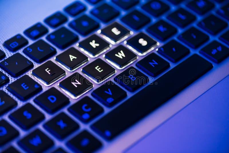 Vals die nieuws op een backlit toetsenbord in een blauw ambiant licht wordt geschreven royalty-vrije stock foto's