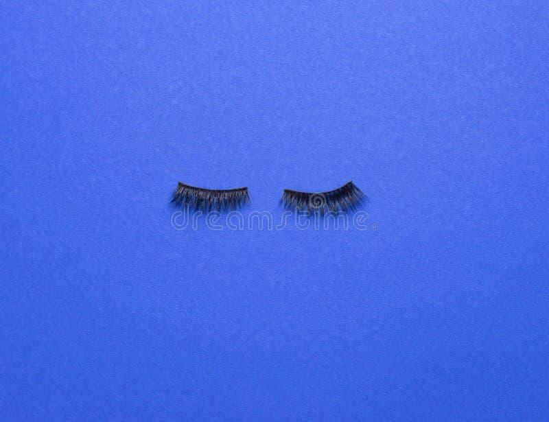 Vals Eyelashes aan de voorzijde van de blauwe achtergrond stock afbeelding