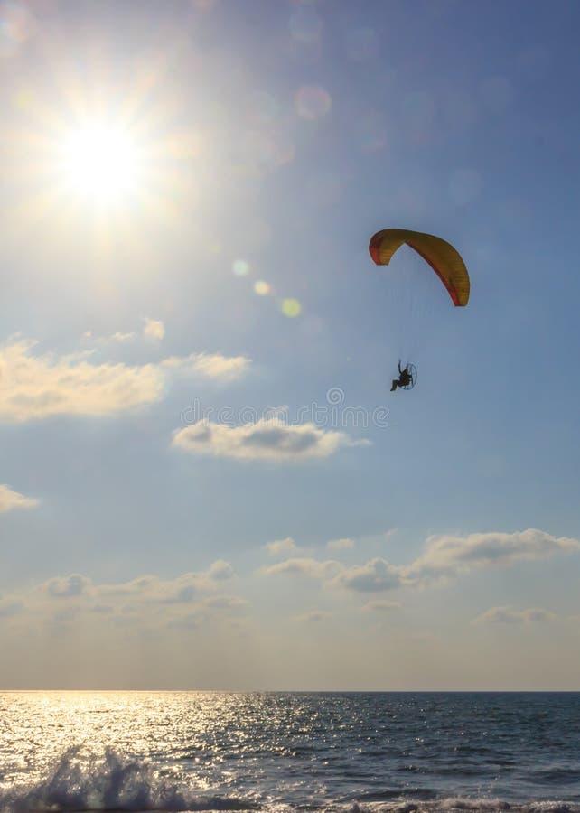 Valschermverbindingsdraad op gemotoriseerd valscherm die over het overzees bij zonsondergang vliegen royalty-vrije stock afbeelding