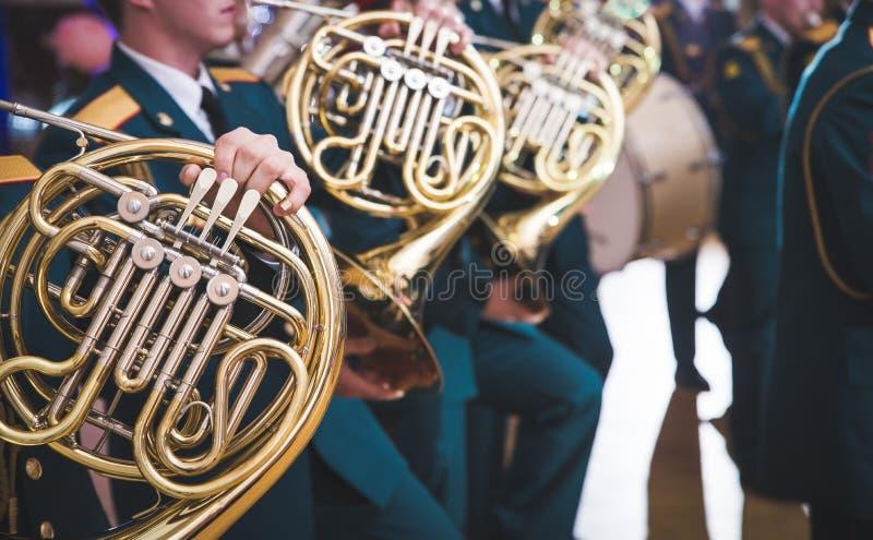 Valthorn- och barnhänder Musikaliska mässingsinstrument, vuxna människor och barn Konsert i skolan royaltyfri bild
