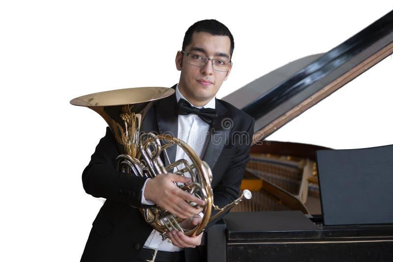 Valthornspelare Hornist som spelar mässingsorkestermusikinstrumentet Isolerat avbilda på vitbakgrund arkivfoton