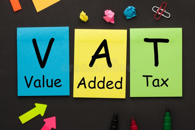 Value Added Tax VAT. Text on color notes and office supplies on black background stock photos