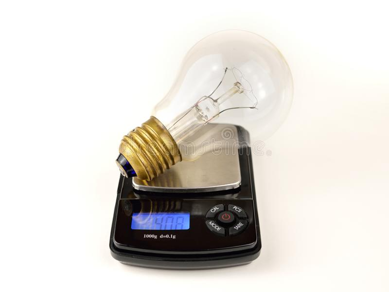 The value of energy. Light bulb on a scale in concept of energy price and ideas value royalty free stock images