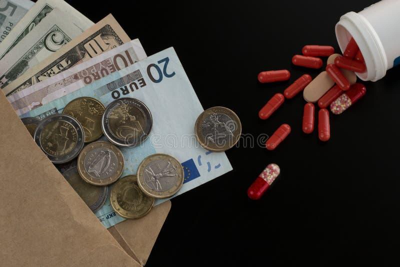 Valuta del dollaro e dell'euro nella busta contro le compresse sparse fotografia stock libera da diritti