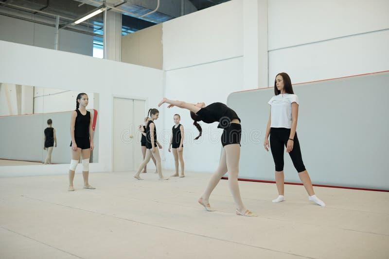 Valutare la flessibilità delle ragazze per la squadra di cheerleader fotografie stock libere da diritti
