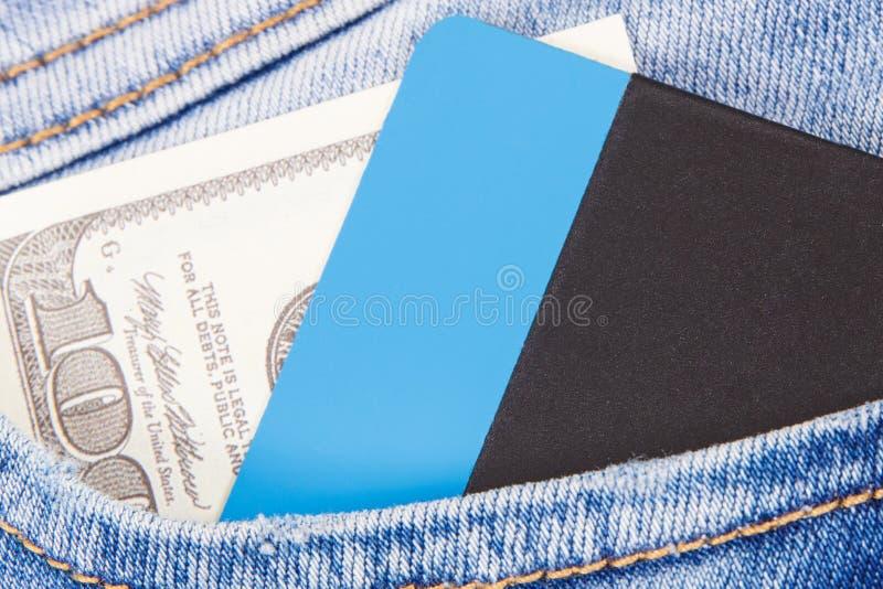 Valutor dollar och kreditkort i jeans stoppa i fickan Val mellan cashless eller kontantbetalning arkivfoton