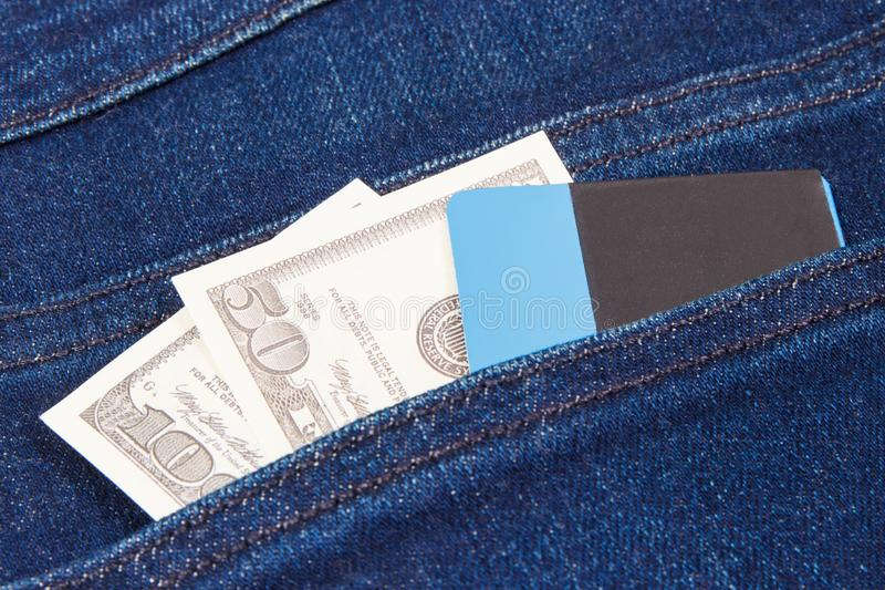 Valutor dollar och kreditkort i jeans stoppa i fickan Val mellan cashless eller kontantbetalning arkivbilder