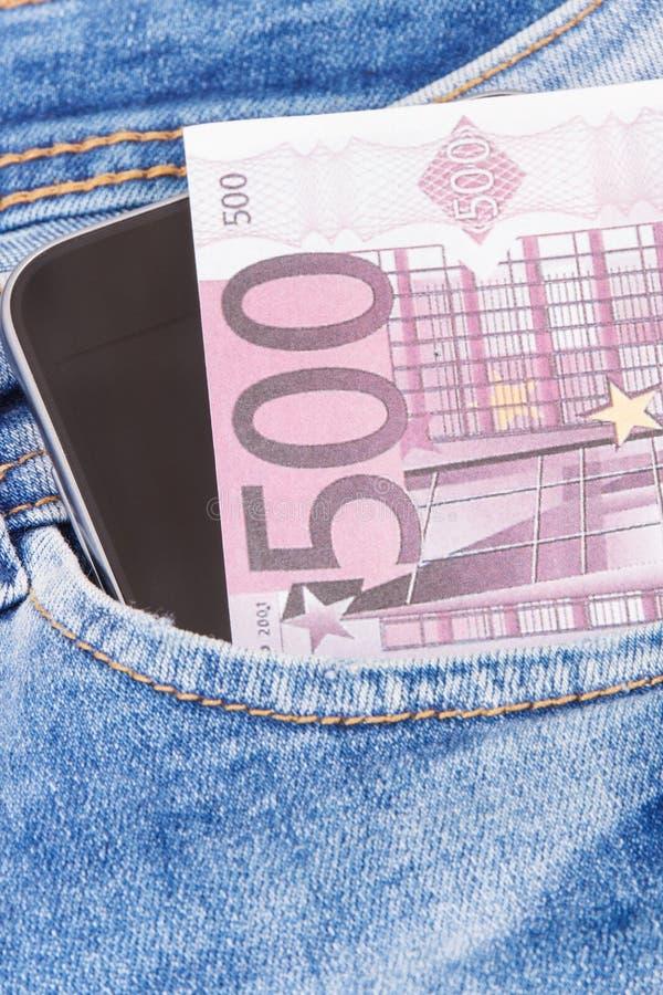 Valutor euro och mobiltelefon för cashless betala i fack av jeans packa ihop finans arkivbilder