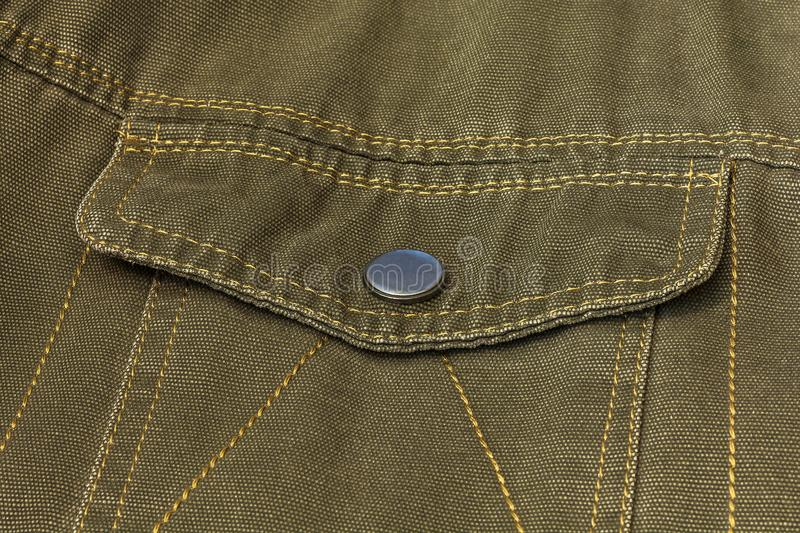 Valve pocket with button clasp on clothes. On the clothing is sewn a pocket valve with a button clasp stock photography