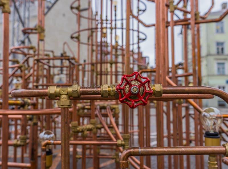 Valve rouge sur la construction de cuivre de tuyau dans extérieur photo stock