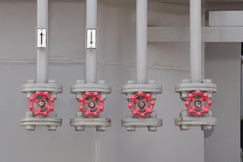 Valves industrielles rouges dans une rangée sur le réseau de pipe-lines gris photographie stock