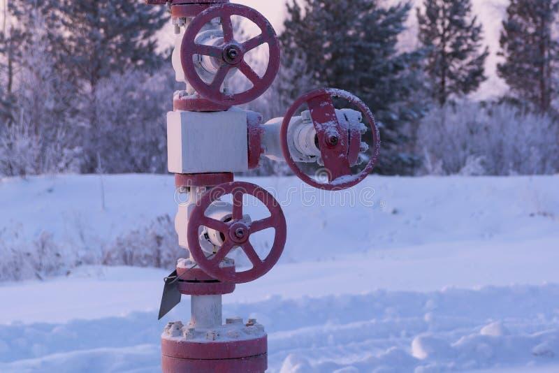 Valvola rossa del petrolio o del gas nell'inverno fotografia stock libera da diritti