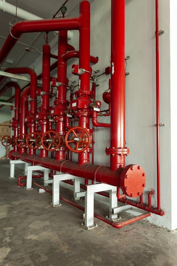 Valvola rossa della tubatura dell'acqua, tubo per controllo della rete di tubazioni dell'acqua e sistema di controllo del tiro in fotografia stock