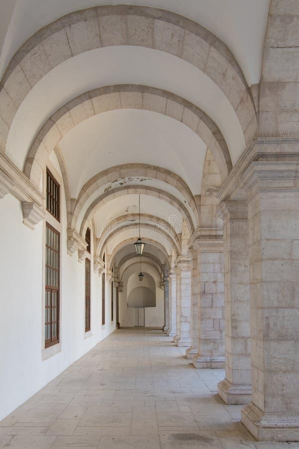Valvport som flyttar sig till perspektivet under bågar med stenkvarterkolonner och en vit vägg arkivfoto