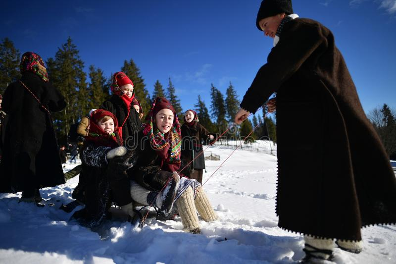 Vama,罗马尼亚, 2017年1月20日:穿传统服装的孩子使用与在高雪的雪橇 库存图片