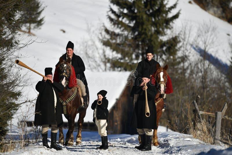 Vama, Romênia, o 20 de janeiro de 2017: Os moradores que jogam pelo chifre longo chamaram o bucium imagens de stock royalty free