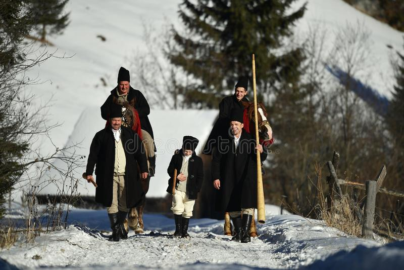 Vama, Romênia, o 20 de janeiro de 2017: Os moradores que jogam pelo chifre longo chamaram o bucium imagem de stock royalty free