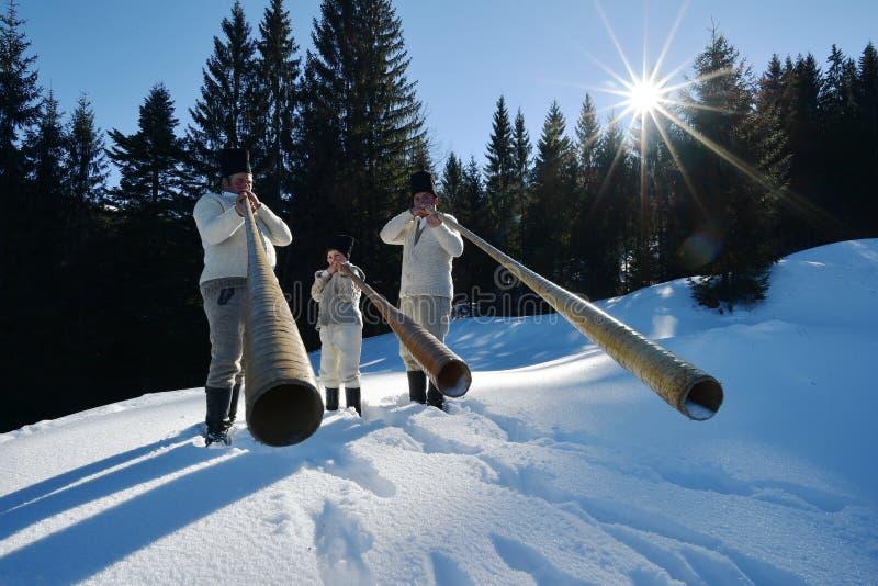Vama, Romênia, o 20 de janeiro de 2017: Os moradores que jogam pelo chifre longo chamaram o bucium foto de stock