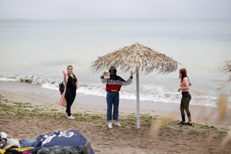 VAMA VECHE, RUMÄNIEN - MAJ 1, 2018: Unga flickor som tar en selfie på stranden, når att ha festat hela natten royaltyfri bild