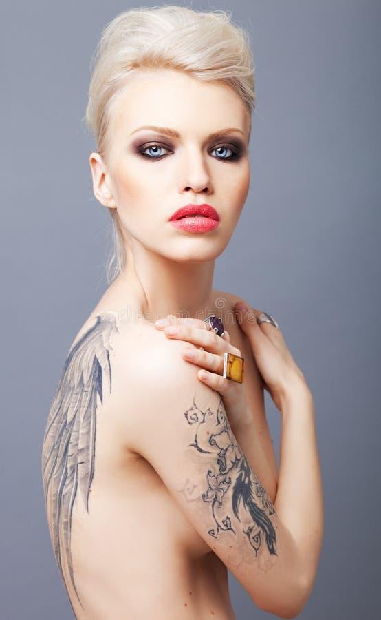 Vamp som ser kvinnan med tatueringen, påskyndar på baksidan royaltyfri foto