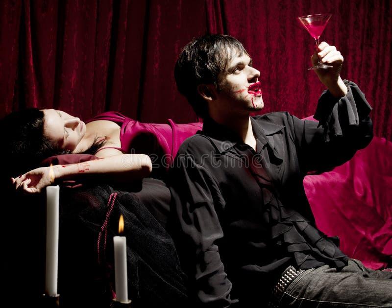 Vampir, der ein blutiges Getränk genießt lizenzfreie stockbilder