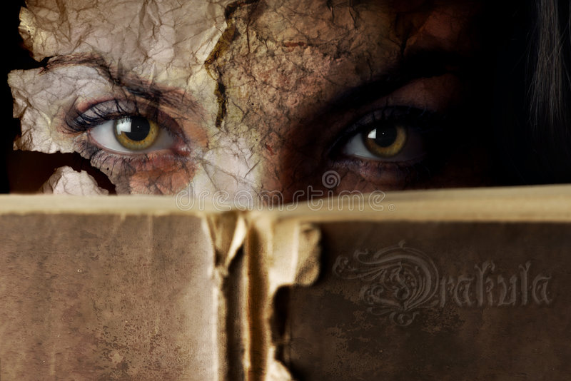 Vampire book. Horror face of the woman covered by the Dracula book stock photo