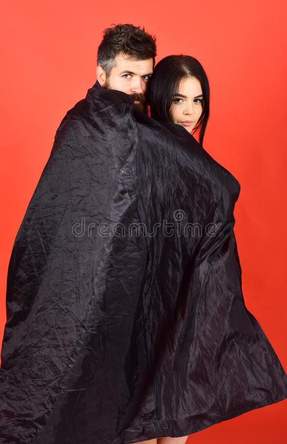 Vampire in cloak behind devil girl. Man and woman dressed like vampire, demon, red background. Couple in love. Vampire in cloak behind devil girl. Man and women stock image