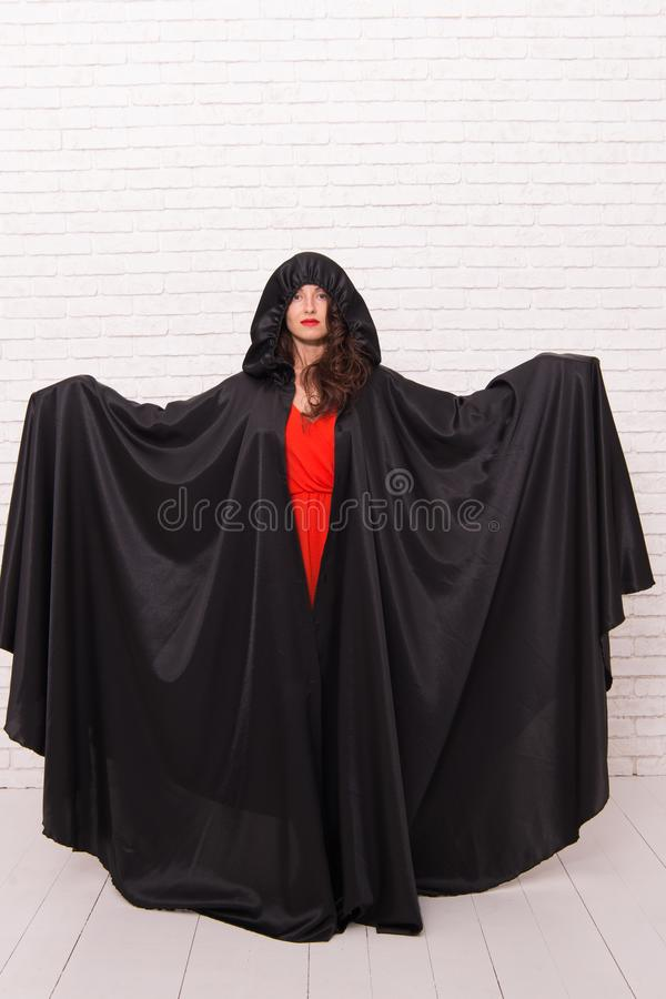 Vampire in cloak sexy devil girl. Woman tempting vampire demon. Girl covered with cloak. Devil concept. Halloween. Masquerade. Halloween party. Damn pretty royalty free stock photos