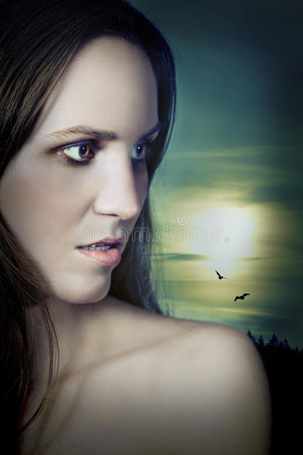 Vampire Girl in Moonlight. Beautiful vampire girl under the moon in profile looking to the side. Novel cover look royalty free stock photo