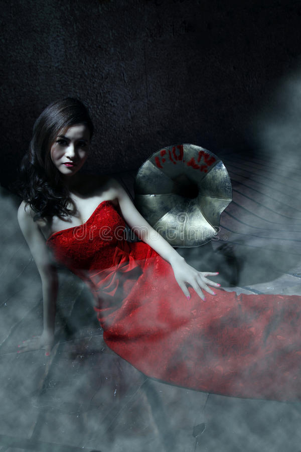 Vampire girl. Wears a red dress royalty free stock photography