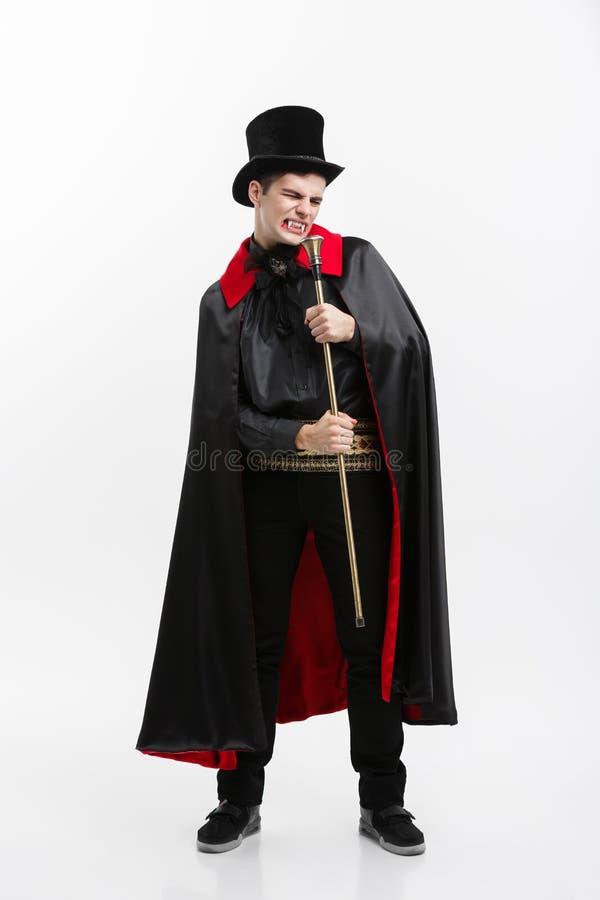 Vampire Halloween Concept - Full length Portrait of handsome caucasian Vampire in black and red halloween costume. stock image
