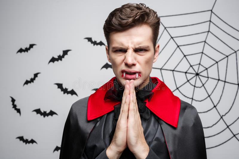 Vampire Halloween Concept - Portrait of handsome caucasian in Vampire halloween costume praying. royalty free stock image