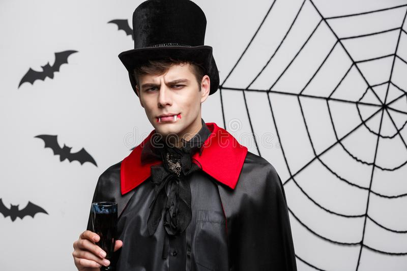 Vampire Halloween Concept - Portrait of Serious handsome caucasian Vampire enjoy drinking bloody red wine. royalty free stock photos