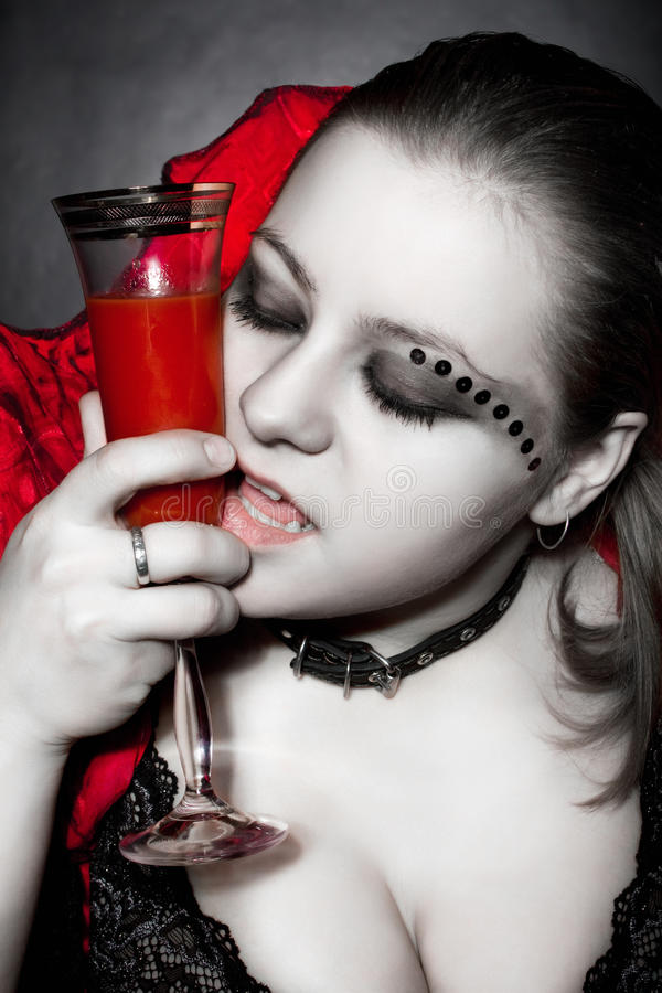 Vampire in red dress with glass full of blood royalty free stock images