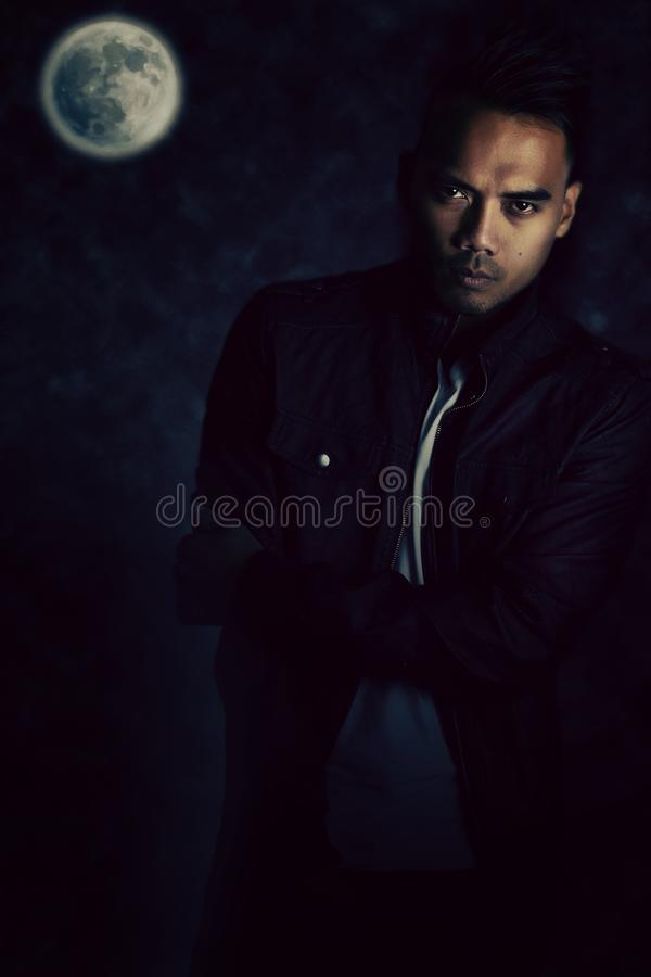 A vampire story. Handsome asian vampire wearing a black leather jacket royalty free stock image