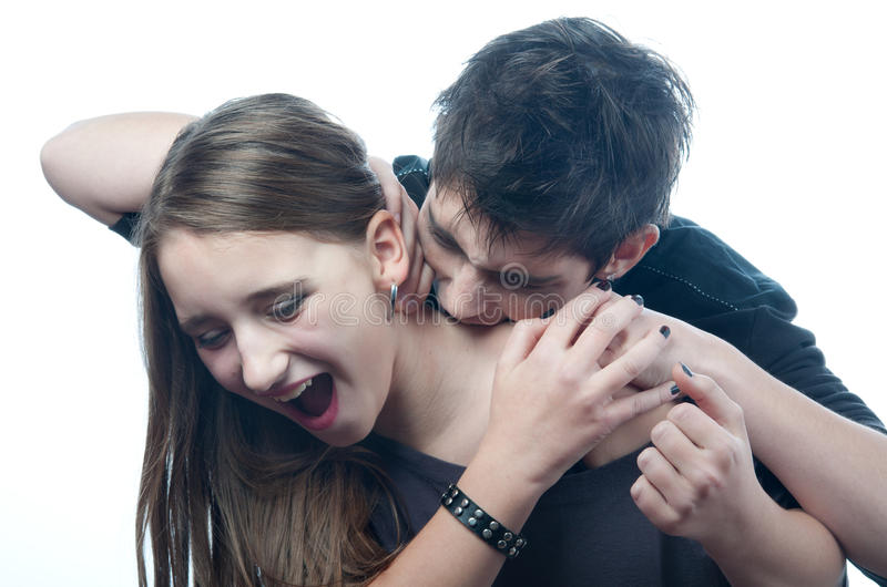 Vampire teenage boy biting neck of teenage girl. Vampire teenage boy biting neck of the frightened teenage girl that tries to defend herself stock images